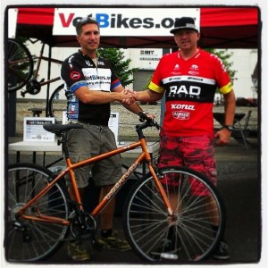 Alex Young accepts a donated bike from Jim Brown and the Kona Bikes.