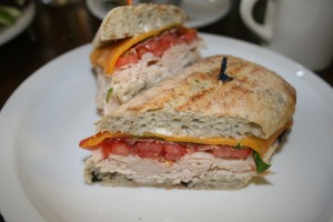 The Rosewood Café's The Wood is a turkey sandwich with smoky bacon and cheese mixed with fresh veggies and basil on a rustic olive roll.