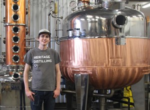 Heritage Distilling Company's 26-year-old Dain Grimmer poses next to Nonna, the distillery's impressive Italian-made copper still. Photo credit: Margo Greenman.