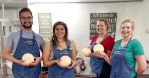 Students Sterling Ingle-Mead, Jennifer Gnau, and Jessica Stone, plus River Valley Cheese owner Kristi Slotemaker posing with their wheels of gouda. © SouthSoundTalk.